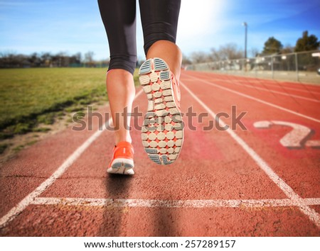 a woman with an athletic pair of legs going for a jog or run during sunrise or sunset - healthy lifestyle concept  - stock photo