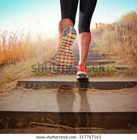 a woman with an athletic pair of legs going for a jog or run during sunrise or sunset up stairs in the mountains - healthy lifestyle concept for urban living  - stock photo