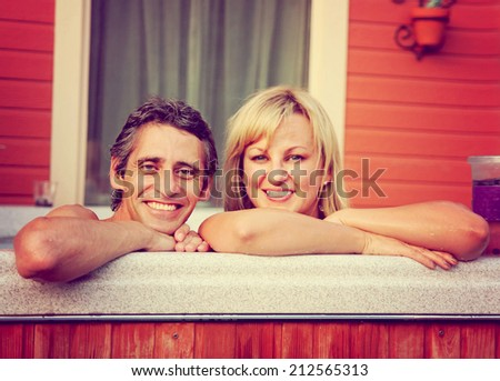 a young couple sitting in hot tub toned with a retro vintage instagram filter  - stock photo