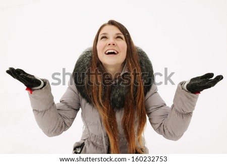 A young woman catches snowflakes in hand - stock photo