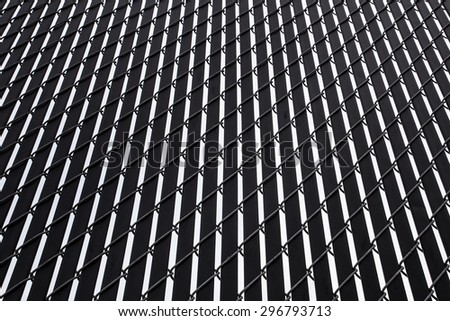 Abstract design of light and dark lines create by metal slats on privacy fence - stock photo