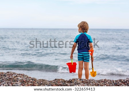 Adorable little blond kid boy standing on lonely ocean beach. Child playing and looking on horizon. Vacations, summer, travel concept. Preschool boy enjoying summer vacations on sea. - stock photo