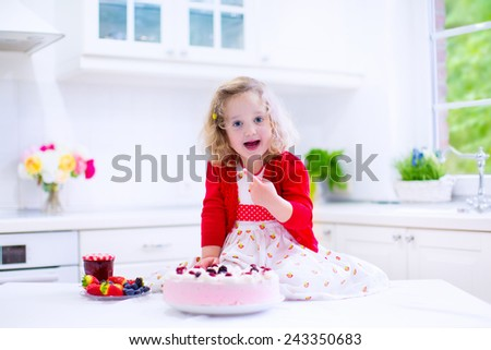 Adorable little girl, cute curly toddler in a red dress, baking and trying fresh strawberry cream cake with fruit and berry in a white kitchen on a sunny summer day - stock photo