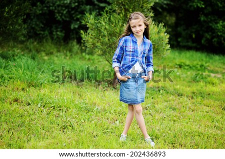 Adorable pre-teen tweenie kid girl with long brunette hair in blu plaid shirt and jeans skirt  waking in the park  - stock photo