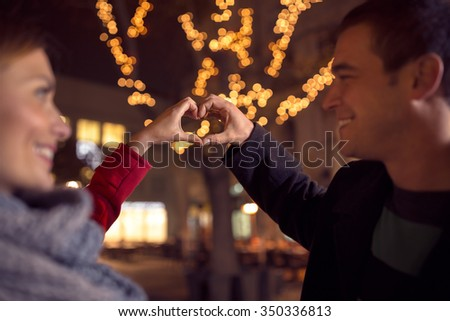 Affectionate couple looking at each other and making heart shape with hands on Christmastime  - stock photo