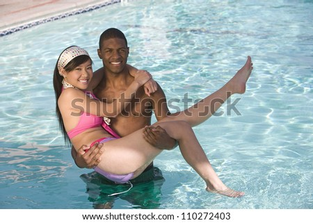 African American man carrying young female in the pool - stock photo