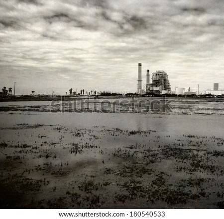aged and worn vintage black and white photo of industrial plant with dramatic sky                              - stock photo
