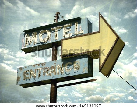 aged and worn vintage motel sign with arrow - stock photo