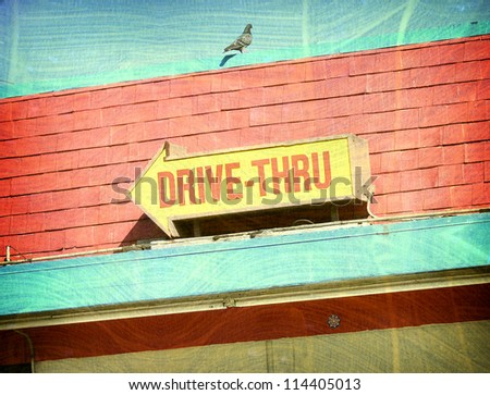 aged and worn vintage photo of drive-thru sign and pigeon - stock photo