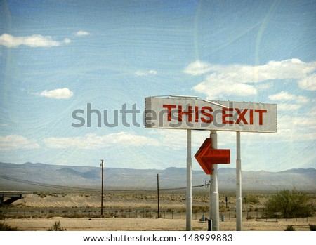 aged and worn vintage photo of exit sign in desert                               - stock photo