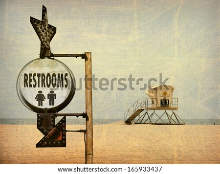 aged and worn vintage photo of lifeguard tower on beach sand and restroom sign                         - stock photo