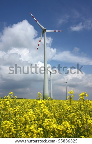 agriculture field and wind mill power turbine under cloudy sky - stock photo