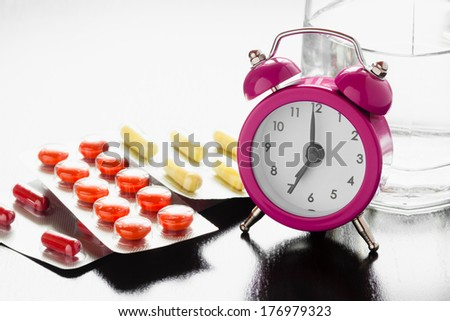 Alarm clock and medical pills on bedside table - stock photo