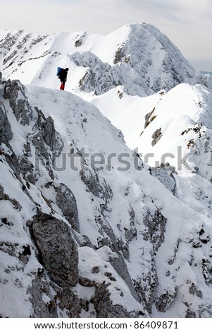 Alpinist climbing a mountain - stock photo