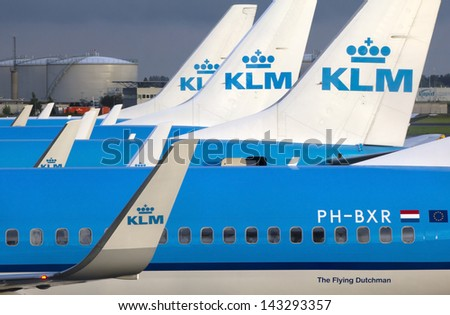 AMSTERDAM - AUGUST 13: KLM planes at Schiphol Airport August 13, 2011 in Amsterdam, The Netherlands. The airport handles over 45 million passengers per year with almost 100 airlines flying from here. - stock photo
