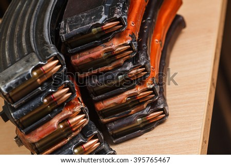 7.62 and 5.56 ammo for machine guns with loaded magazines 7.62 ammo for machine guns with loaded magazines on table - stock photo