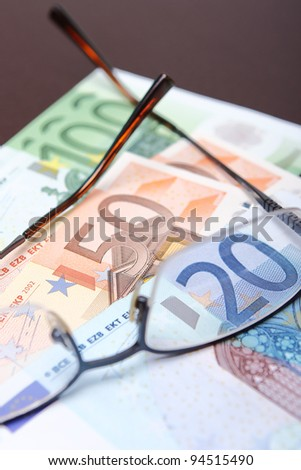 20, 50, and 100 euro bank notes with a pair of glasses - stock photo