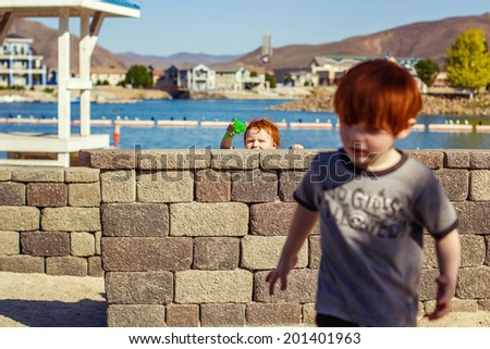 4 and 2 year old brothers playing at a park -- image taken at Sparks Marina Park in Sparks, Nevada, USA - stock photo