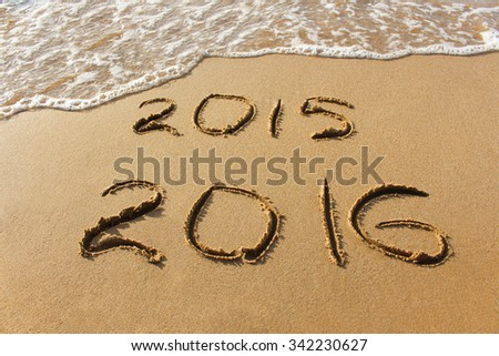 2015 and 2016 year written on sandy beach sea.  - stock photo