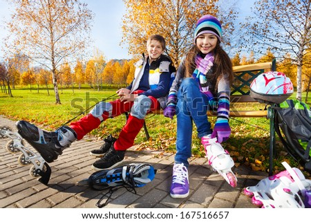 10 and 11 years old couple of school kids, boy an girl putting on roller blades in warm autumn clothes in the park shoot from low angle - stock photo