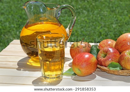 Apple juice in a glass with a pitcher and apples on a wood table  - stock photo