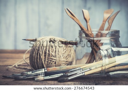 Art and craft tools. Artist's brushes, sculpturing set and pencil in glass jars on rustic background. Selective focus. - stock photo