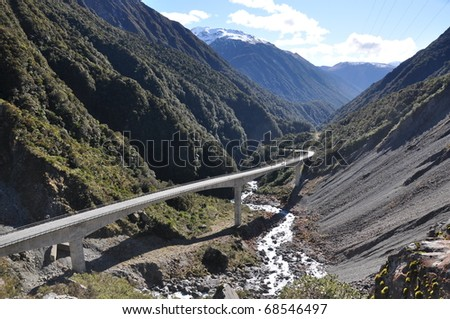"""Arthurs Pass"" South Island, New Zealand. Highway winds it way through the Alps of New Zealand joining the east and west coasts of the South Island. August 2010. - stock photo"