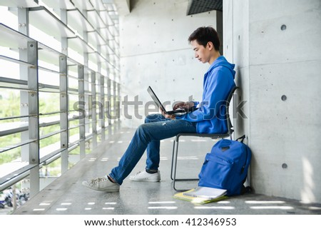 asian college student sitting student with laptop on campus - stock photo