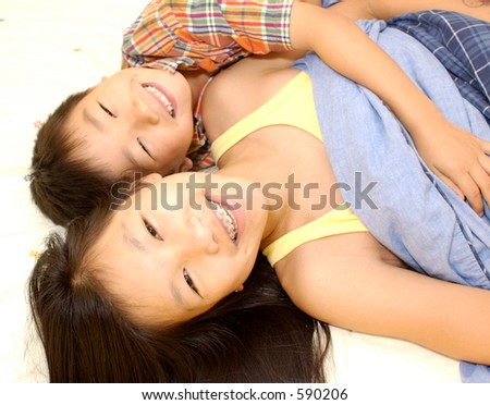 2 asian siblings lying in a bed smiling - stock photo