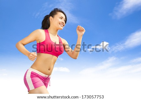 asian smiling runner woman jogging in sunny day - stock photo