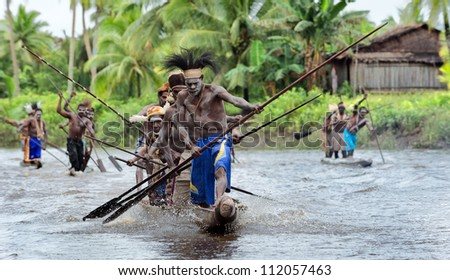 ASMAT PROVINCE, JOW VILLAGE, INDONESIA, NEW GUINEA - JUNE 28: The Asmat Warriors  with a spear-oars on the dugout canoes. On June 28, 2012 in Jow Village, Asmat province, New Guinea, Indonesia - stock photo