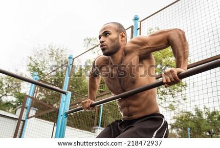 athlete doing pull-up on horizontal bar.Mans fitness at the stadium  - stock photo