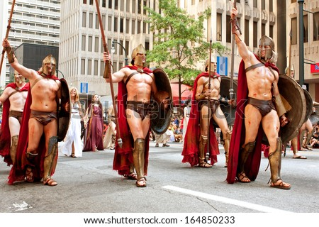 """ATLANTA, GA - AUGUST 31:  Several men representing Spartan warriors from the movie """"300"""" salute the crowd while walking in the annual Dragon Con parade, on August 31, 2013 in Atlanta, GA.  - stock photo"""
