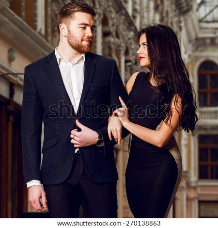 Attractive couple in love in elegant glamour  outfit walking in old town street . Pretty brunette woman with red lips  in long cocktail  dress and her handsome boyfriend have time off. - stock photo