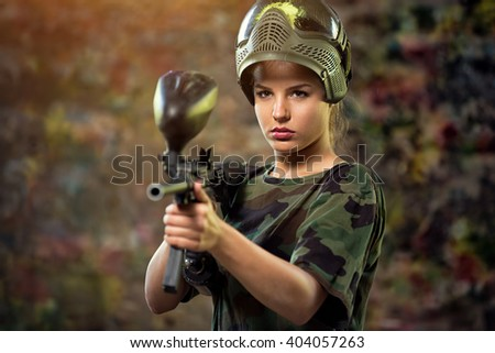 attractive female paintball targeting with gun  - stock photo