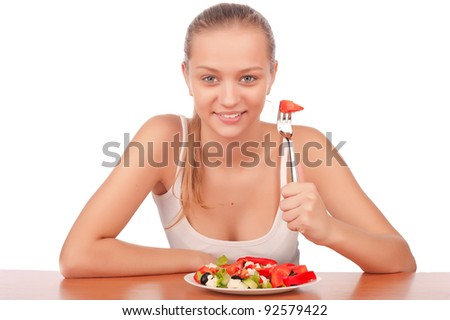 attractive young woman eat vegetarian salad at table, isolated on white - stock photo