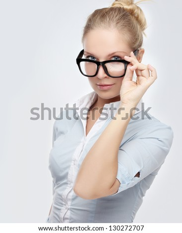 Attractive young woman pulls down here eye glasses  while pouting at the camera. - stock photo