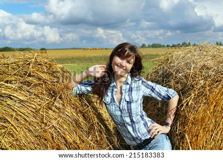 Autumnal nature; Happy woman in haystacks on fields  - stock photo