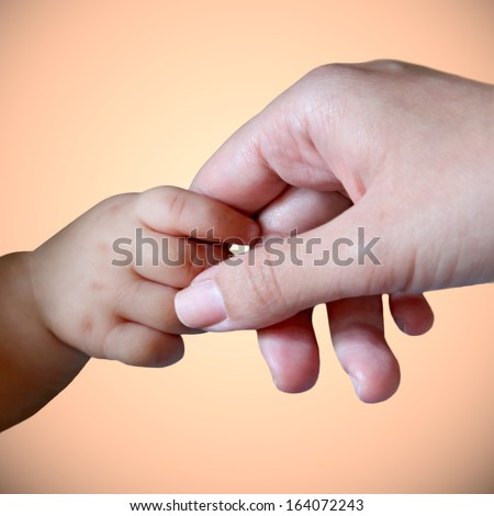 Baby hand gently holding mother's finger - stock photo