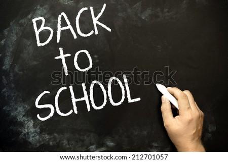 Back to school blackboard, chalkboard. Teacher writing back to school on black chalk board. - stock photo