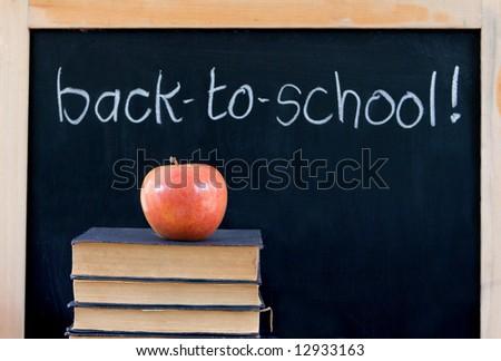 """back-to-school"" written on chalkboard - with apple & books - stock photo"