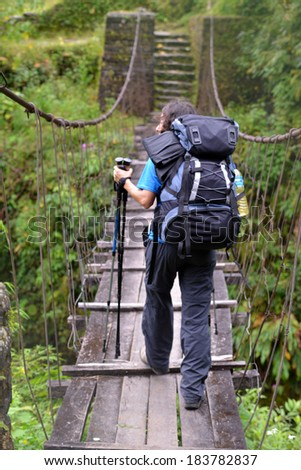 Back view of a trekker woman passing on a suspension bridge in the Himalayas - stock photo