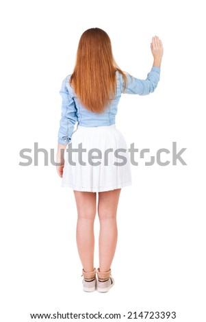 back view of woman. Young woman in dress presses down on something. Isolated over white background. Rear view people collection. backside view of person. she holds his hand open, palm forward - stock photo