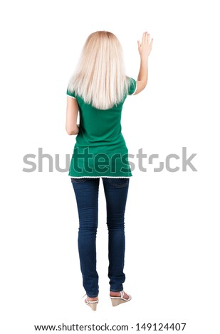 back view of woman. Young woman in jeans presses down on something. Isolated over white background. Rear view people collection. backside view of person. she holds his hand open, palm forward - stock photo
