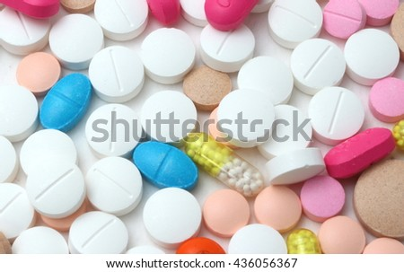 Background of assorted pharmaceutical capsules and medication in different colors denoting different drugs and antibiotics in a health care concept  - stock photo