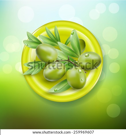background with green olives on a green plate - stock photo
