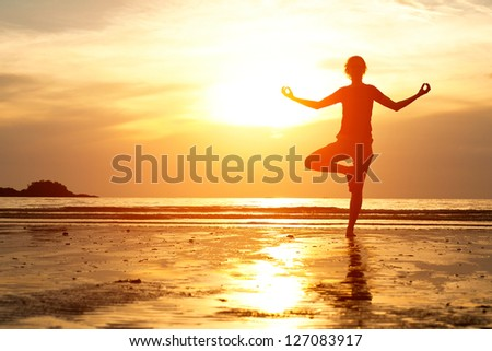 Backlit, young woman practicing yoga on the beach at sunset. - stock photo