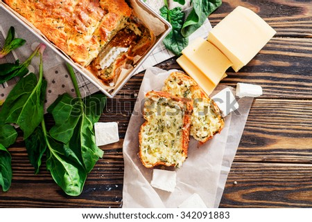 baked cheese pie with spinach , feta and fresh ingredients on a wooden background - stock photo