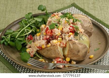 baked jacket potato with tuna salad and watercress                           - stock photo