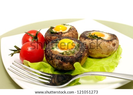 Baked mushrooms with quail`s eggs and tomatoes - stock photo